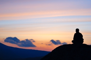 Man meditating on the hill.